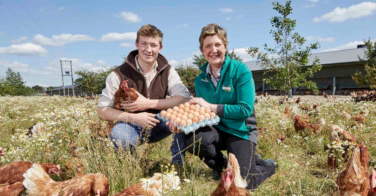 Morrison's Sophie Throup with an unknown man holding eggs on a poultry farm