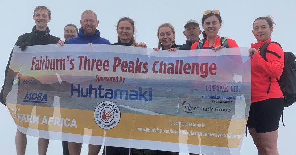 The fairburns team atop a peak